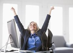 Happy Caucasian businesswoman with feet up on desk Stock Photos