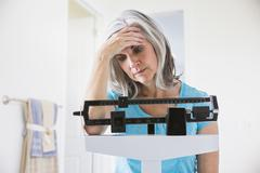 Unhappy Caucasian woman standing on weight scale Stock Photos