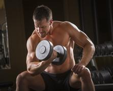 Caucasian man doing biceps curls with dumbbell in gym Stock Photos