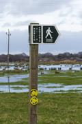 Footpath sign with floods Stock Photos