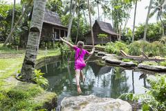 Caucasian girl swinging on rope in garden, Ubud, Bali, Indonesia Stock Photos