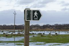 footpath sign with floods - stock photo