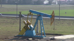 Oil pumpjack, donkey pumper near main road, oil well pump, crude oil, drilling Stock Footage