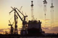 Stock Photo of Cranes and a Tanker Moored at a Harbour at Sunset