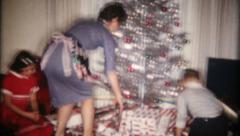 67 - family of four gathers on Christmas morning - vintage film home movie Stock Footage