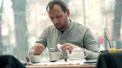 Happy young man adding sugar into tea in cafe HD Stock Footage