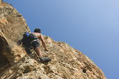 Male free climber scaling rock face rear view upward view Stock Photos