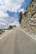 Mountain road running to vanishing point Stock Photos