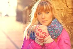 Woman warming her hands in mittens - stock photo