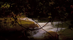 View of Small Cascade Waterfall Through Trees in a Jungle in Thailand Stock Footage
