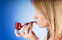 Girl smoking pipe against the gradient background Stock Photos