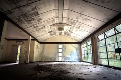 Abandoned building interior with leaf-strewn floor Stock Photos
