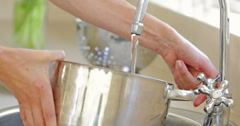 Woman filling pot with water from the tap Stock Footage