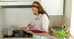 Pretty woman reading a recipe while making dinner Stock Footage