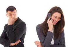 Suspicious man looking at his woman talking on the phone Stock Photos