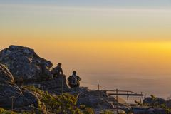 two people watching sunset on table mountain - stock photo