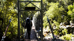 Hiker on swing bridge Stock Footage