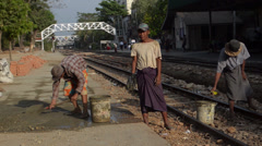 TRAIN WORKERS: 3-shot workers fixing train platform Stock Footage