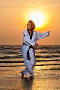 Martial arts man training taekwondo at sunset - stock photo