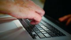 Man typing on a laptop shot with a narrow depth of field and close-up. Stock Footage