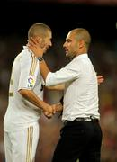 Karim Benzema of R Madrid and FC Barcelona coach Guardiola - stock photo