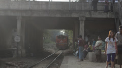 TRAIN LOCOMOTIVE: Train approaches underpass-passengers on platform - stock footage