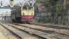TRAIN - LOCOMOTIVE: Track level view of yellow train approaching with footbridge - stock footage