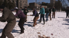 College and university students playing tug of war in the snow Stock Footage