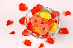 colored candies with two red hearts in glass bowl and rose petals - stock photo