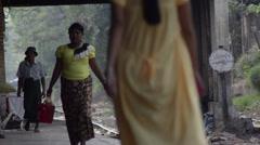 TRAIN LOCOMOTIVE: Telephoto view of people walking on train platform - stock footage