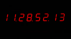 A digital red clock isolated on a black background counting the time Stock Footage