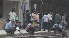 TRAIN LOCOMOTIVE: Passengers squat and wait on platform's edge - stock footage