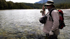 fisherman netting a brown trout - stock footage