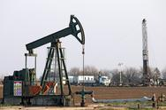 Stock Photo of oilfield with pump jack and oil drilling rig