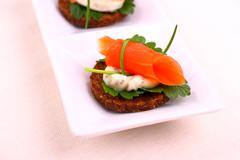 smoked salmon roll on pumpernickel bread with remoulade - stock photo