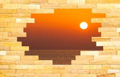 Crashed brick wall with beautiful sun set over the sea behind Piirros