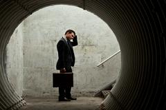 Desparate businessman holding his head in a dark tunnel. Stock Photos