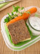 Lunchbox with wholemeal bread and carrots with yogurt dip - stock photo