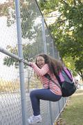 Portrait of enthusiastic Hispanic school girl climbing fence Stock Photos