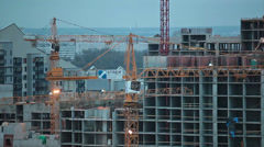 Construction cranes moving over building Stock Footage