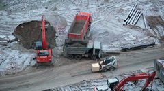 Construction site with machinery: lorries, excavator, loader. Stock Footage