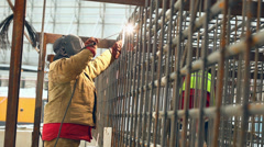 Welder at work, welding a metal framework pile - stock footage