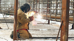 Professional welder welding a metal framework pile, using a mask - stock footage