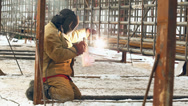 Stock Video Footage of Professional welder welding a metal framework pile, using a mask