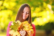 Stock Photo of fall season. portrait girl woman with bunch of autumnal leaves