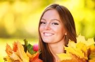 Stock Photo of fall season. portrait girl woman holding autumnal leaves in park