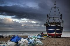 Fishing boat on beach landscape with stormy sky Stock Photos