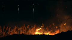 Dry marsh grasses burn at night in the distance lights reflected in the lake Stock Footage