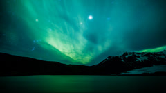 Northern lights (Aurora Borealis) over a glacier in Iceland Stock Footage