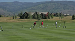 Golfers practice at a golf course driving range in Idaho Stock Footage
